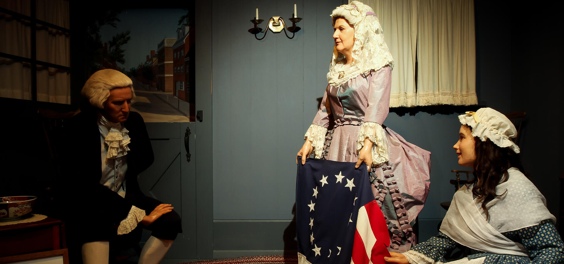 George Washington, with his wife Martha, and Betsy Ross looking at the first American Flag.